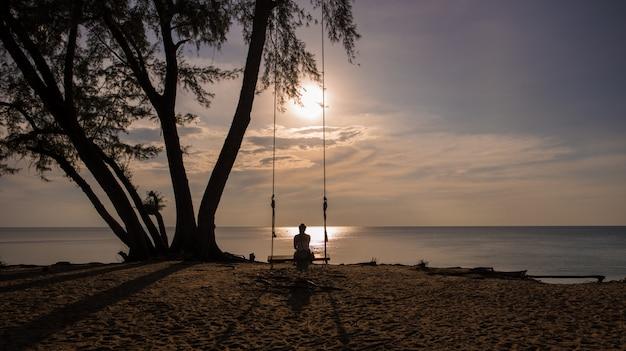 Mulher que balança na praia, tailândia.