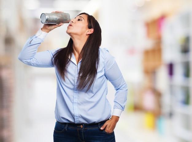 Mulher que bebe de uma garrafa de água