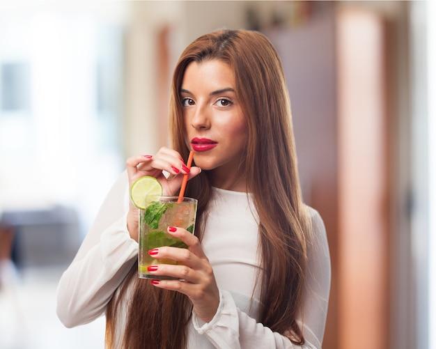 Mulher que bebe uma bebida com uma palha