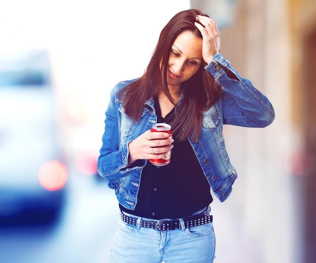Mulher que bebe uma coca-cola