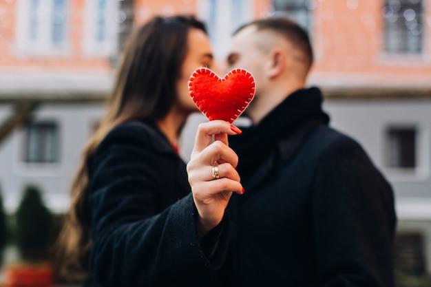 Mulher que beija o homem enquanto mostra o coração vermelho