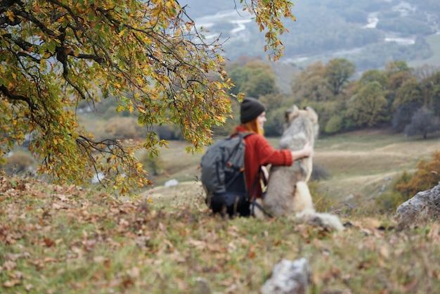 Mulher que caminha ao lado de um cachorro nas montanhas e admira a paisagem natural
