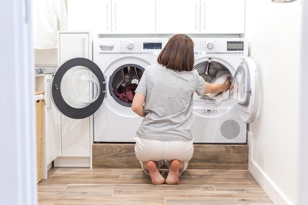 Mulher que carrega a roupa suja na máquina de lavar para lavar na despensa moderna