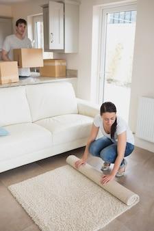 Mulher que coloca o tapete com o homem segurando caixas móveis