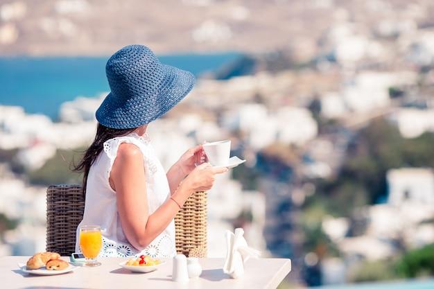 Mulher que come o café da manhã no café exterior com vista surpreendente na cidade de mykonos.