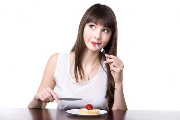 Mulher que come um bolo