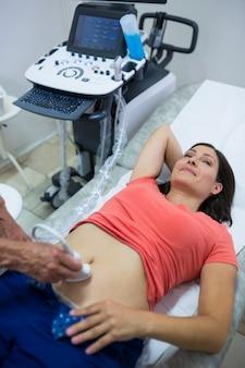 Mulher que começ o ultra-som de um abdômen de médico