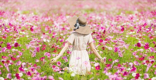 Mulher que corre nas flores do jardim flores do cosmos para tocá-la.