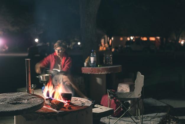 Mulher que cozinha com madeira do fogo e equipamento do braai em a noite. barraca e cadeiras em primeiro plano. aventuras em parques nacionais africanos. imagem enfraquecida.