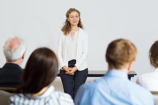 Mulher que dá uma palestra para uma audiência