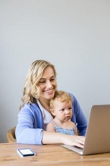 Mulher que datilografa em um laptop com um bebê nas pernas