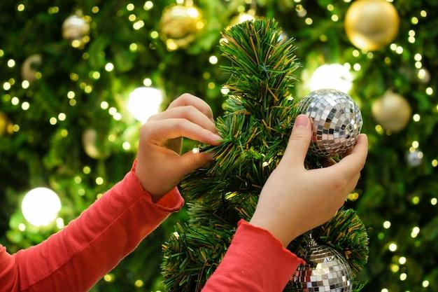Mulher que decora a árvore de natal no tema da prata e do ouro.