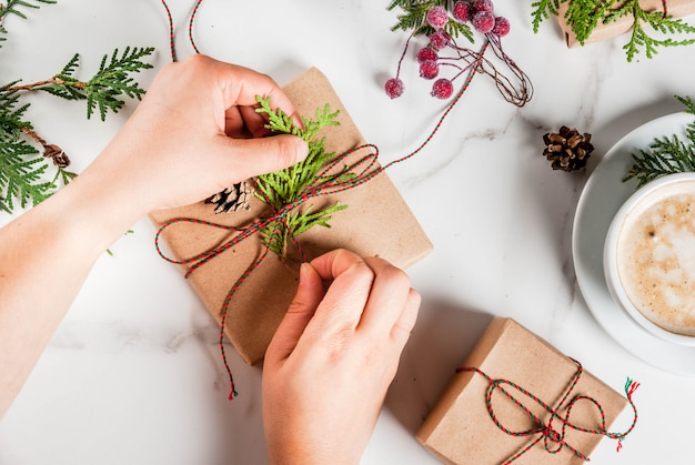 Mulher que decora o presente de natal ou a caixa de presente com galhos de árvores de natal pinhas bagas vermelhas na mesa de mármore branca ou para fazer a lista no caderno com caneca de café