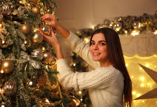 Mulher que decora os brinquedos de ano novo da árvore de natal em casa preparação para celebração