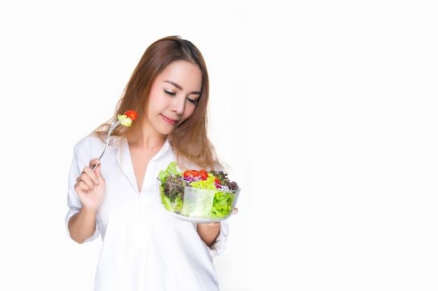 Mulher que desgasta uma bacia branca que prende uma bacia de salada.
