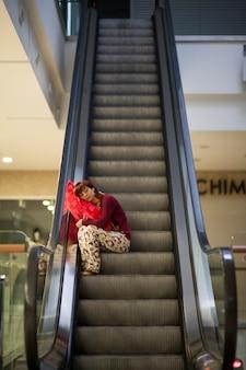 Mulher que dorme em escadas de centro comercial