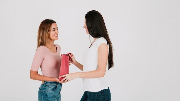 Mulher que entrega saco de papel para a namorada