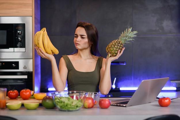 Mulher que escolhe entre a sobremesa e as frutas na mesa na cozinha. dieta saudável