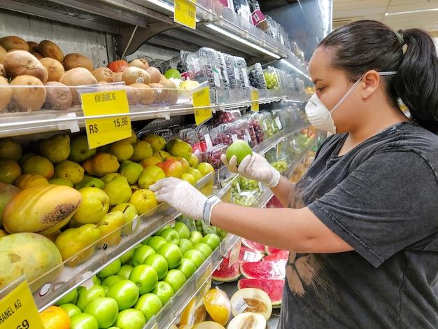 Mulher que escolhe maçãs verdes com máscara e luva, proteção contra coronavírus.