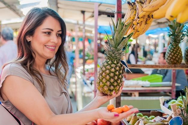 Mulher que escolhe o abacaxi durante as compras no mercado verde dos vegetais frutíferos. atraente mulher de compras. bela jovem pegando, escolhendo frutas, abacaxis.