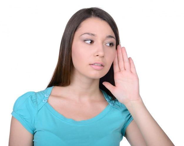 Mulher que escuta a bisbolhetice quando isolado no branco.