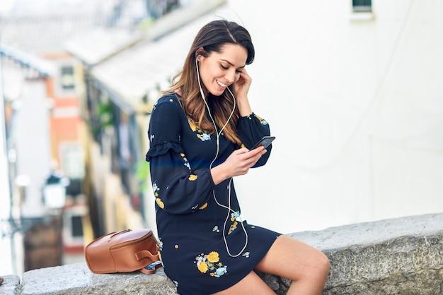 Mulher que escuta a música com fones de ouvido e o telefone esperto ao ar livre.