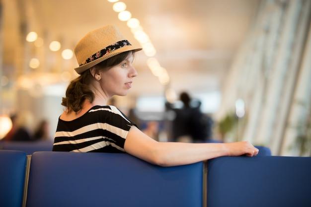 Mulher que espera no aeroporto