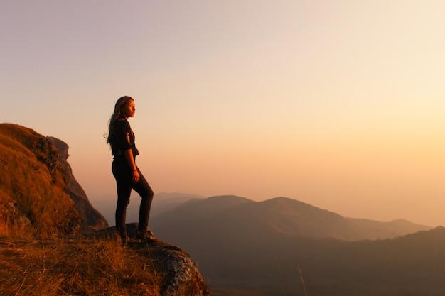 Mulher que está em uma montanha que olha no por do sol