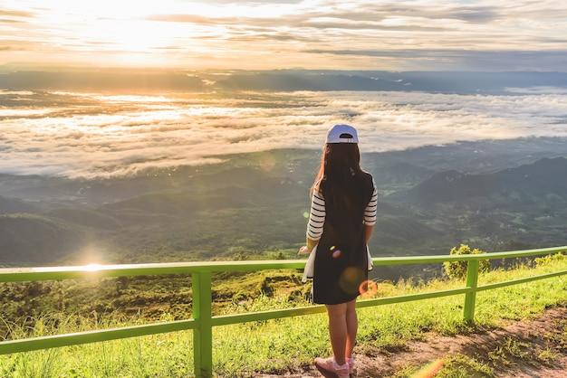 Mulher que está sozinho no penhasco sobre a paisagem de montanha e olhando para a névoa