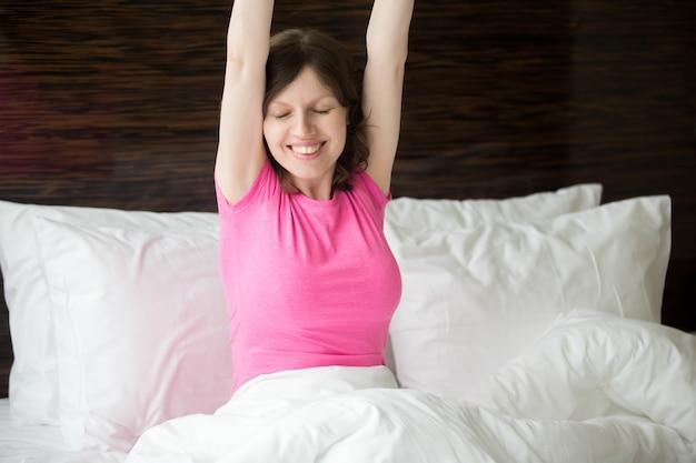 Mulher que estica os braços na cama