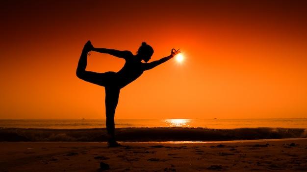 Mulher que estica seu corpo em posturas de yoga ao pôr do sol na praia