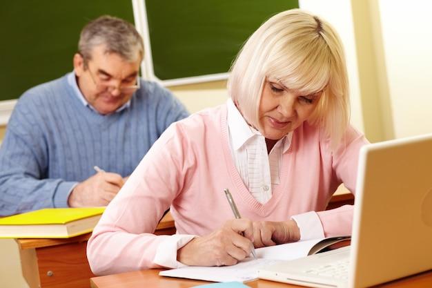 Mulher que estuda com seu fundo marido
