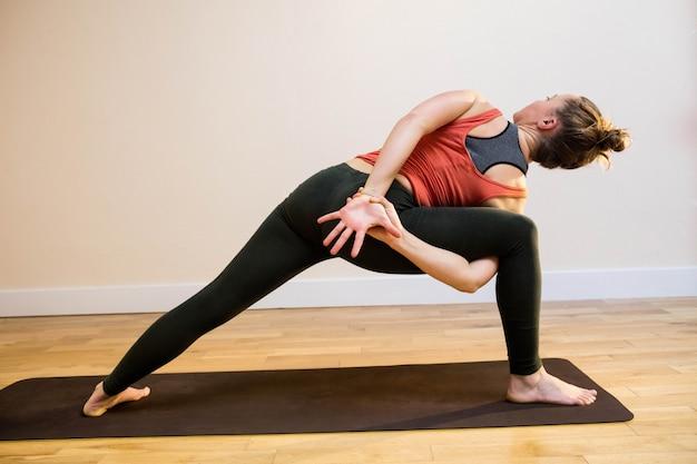 Mulher que executa ângulo lateral ligada colocam na esteira do exercício