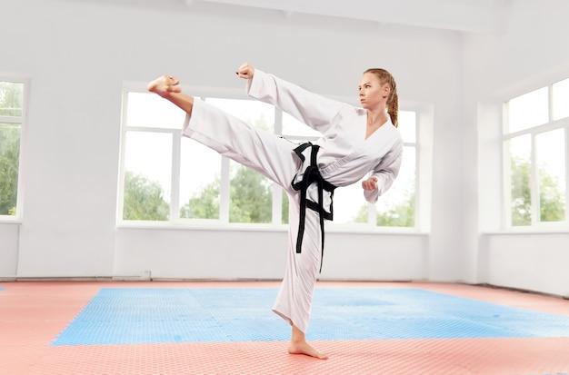 Mulher que executa artes marciais chute alto na aula de luta.