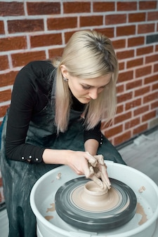 Mulher que faz a cerâmica cerâmica na roda, mãos closeup. conceito de mulher em freelance, negócios, hobby