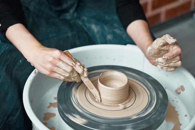 Mulher que faz a cerâmica na roda, close-up das mãos, criação de mercadorias cerâmicos. trabalho manual
