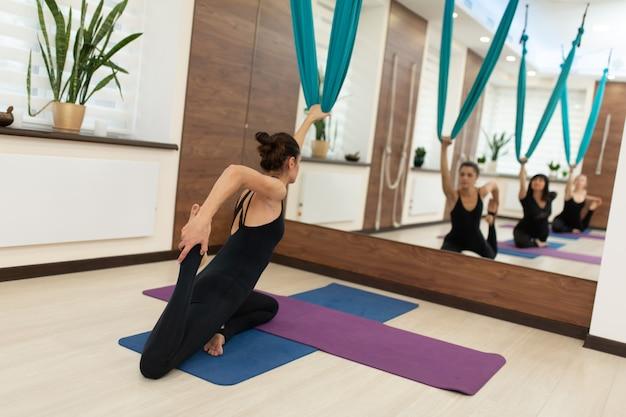 Mulher que faz a ioga da mosca que estica exercícios no gym. estilo de vida em forma e bem-estar.