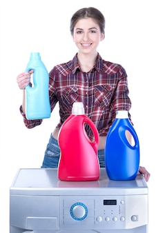 Mulher que faz a lavanderia na máquina de lavar.