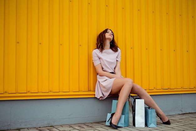 Mulher que faz compras de beleza com sacos de papel ao ar livre