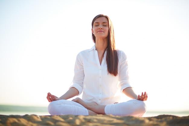 Mulher que faz exercícios de ioga na praia