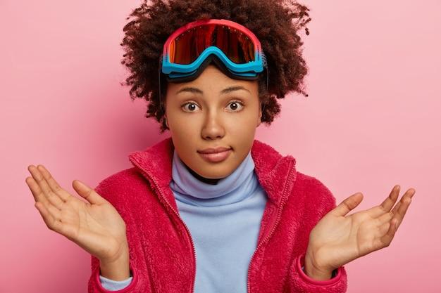 Mulher que faz férias sem noção, abre as palmas das mãos com hesitação, usa máscara de esqui na cabeça, roupa casual, poses dentro de casa