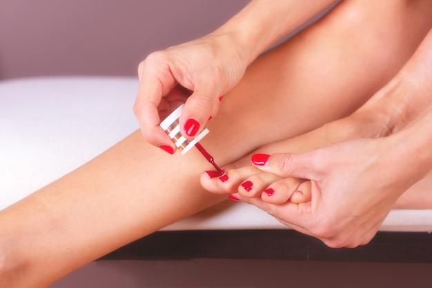 Mulher que faz o cuidado de pés e o tratamento do prego aplicando esmalte vermelho.