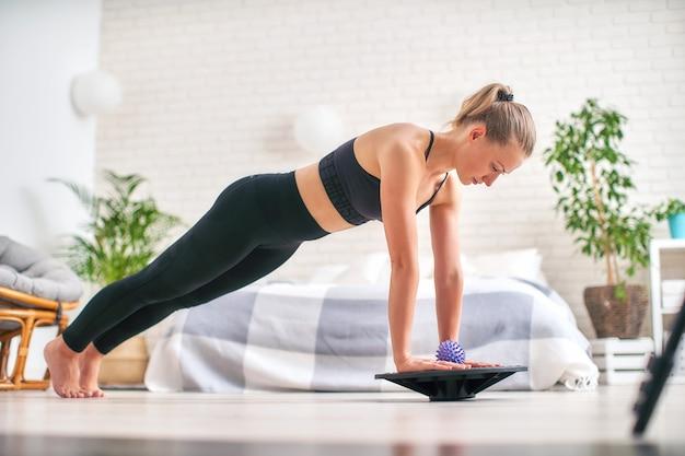 Mulher que faz o exercício em um equilibrador especial do simulador.
