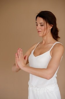 Mulher que faz o namaste em um fundo bege no estúdio. meditação. dia internacional da ioga