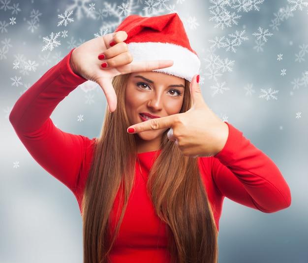 Mulher que faz um frame com seus dedos em um fundo de flocos de neve