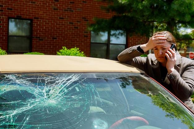 Mulher que faz um telefonema ao lado do carro danificado após um acidente de transito