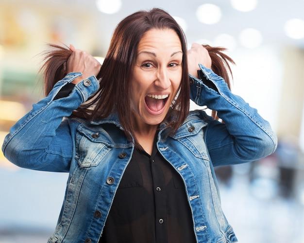 Mulher que grita e que puxa seu cabelo