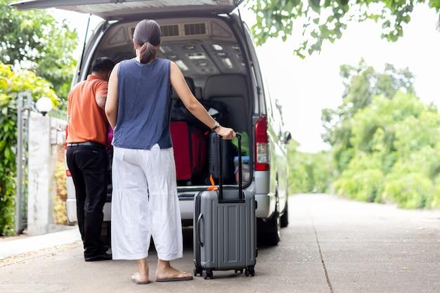 Mulher que guarda a bagagem com o motorista que põe a bagagem no mini conceito do curso do ônibus.