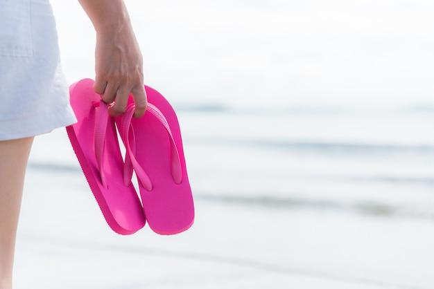 Mulher que guarda o falhanço de aleta cor-de-rosa no sandy beach para o conceito do verão.
