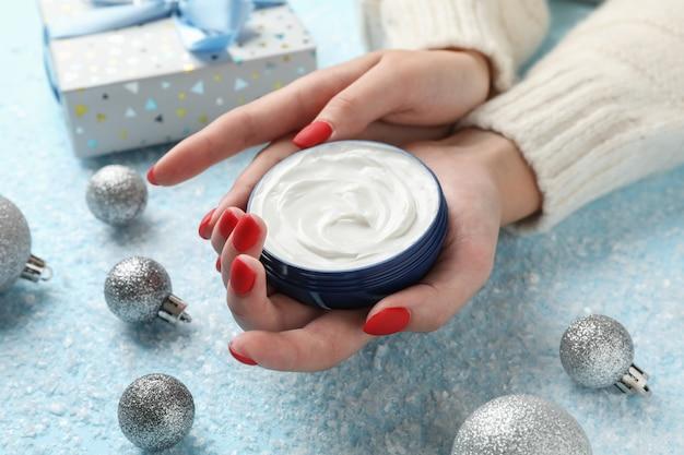 Mulher que guarda o frasco do creme do inverno para a pele, caixa de presente no fundo azul nevado, espaço para o texto. fechar-se